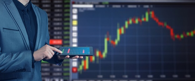 Person holding a tablet with stock exchange charts
